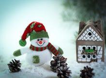 Juegue el muñeco de nieve y una casa de pan de jengibre en un fondo ligero Fotografía de archivo