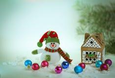 Juegue el muñeco de nieve y una casa de pan de jengibre en un fondo ligero Imagen de archivo libre de regalías