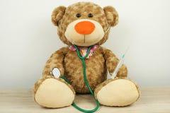 Juegue el oso con el estetoscopio y la jeringuilla/el pediatra foto de archivo