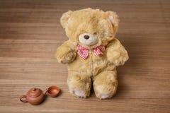 Juegue el oso de peluche y caldera y taza de té en fondo de madera Foto de archivo