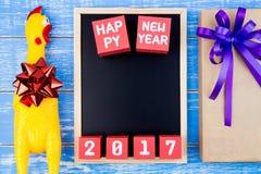 Juegue el pollo amarillo, la actual caja de regalo, la pizarra y nueva y feliz Foto de archivo libre de regalías