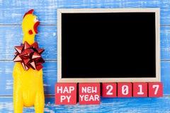 Juegue el pollo, la pizarra y el número amarillos de la Feliz Año Nuevo 2017 encendido Fotos de archivo
