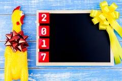 Juegue el pollo, la pizarra y el número amarillos de la Feliz Año Nuevo 2017 encendido Foto de archivo
