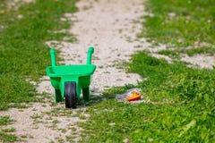 Juegue la carretilla con la pala en la hierba, juguete abandonado Imagen de archivo libre de regalías