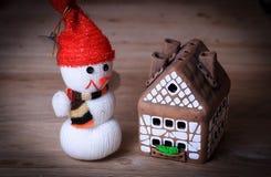 Juegue la casa de pan de jengibre del muñeco de nieve y en la tabla de la Navidad Imagen de archivo libre de regalías