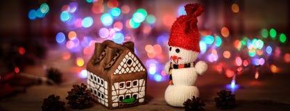 Juegue la casa de pan de jengibre del muñeco de nieve y en la tabla de la Navidad Imagenes de archivo