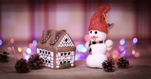 Juegue la casa de pan de jengibre del muñeco de nieve y en la tabla de la Navidad Imágenes de archivo libres de regalías