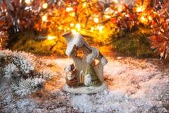 Juegue la casa que se coloca en la nieve en un fondo de las ramas borrosas de la luz y del abeto con nieve Foto de archivo