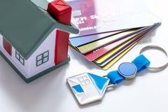 Juegue la casa, tarjetas de crédito - hipoteca del concepto en el fondo blanco imagen de archivo libre de regalías