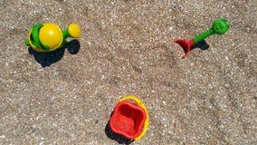 Juegue la pala, el cubo y la regadera en la costa de mar Imagenes de archivo