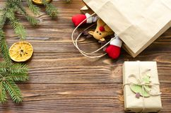 juegue los ciervos en la bolsa de papel de Kraft, caja de regalo, abeto en la tabla de madera Fotos de archivo libres de regalías