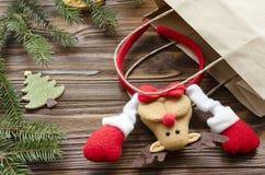 juegue los ciervos en la bolsa de papel de Kraft, caja de regalo, abeto en la tabla de madera Imagen de archivo libre de regalías