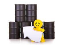 Juegue los soportes del hombre cerca de los barriles con aceite y asimientos el indicador hacia arriba imagenes de archivo