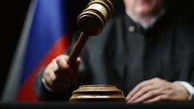 Juez con el mazo en su mano que martilla contra la bandera rusa y el sitio negro del fondo ante el tribunal almacen de metraje de vídeo