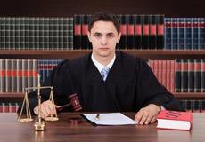 Juez masculino confiado que se sienta en sala de tribunal Imágenes de archivo libres de regalías