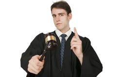 Juez que aumenta el dedo índice en blanco Foto de archivo libre de regalías
