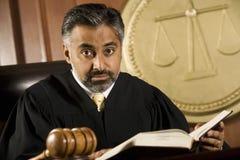 Juez Reading Law Book en sala de tribunal Fotografía de archivo