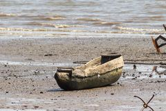 One person boat lying on shore. JUFUREH, GAMBIA- JAN 12, 2014: Boat to row are made from 1 tree, lying on shore royalty free stock images