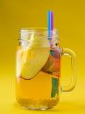 Jug of apple juice on yellow Royalty Free Stock Photo