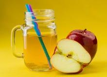 Jug of apple juice on yellow Stock Photos