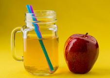 Jug of apple juice on yellow Royalty Free Stock Images