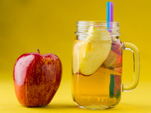 Jug of apple juice on yellow Royalty Free Stock Photos