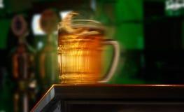 Jug of beer at the bar. A beer jug moving along the counter Royalty Free Stock Images