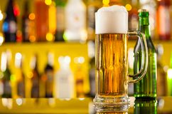 Jug of beer with bottle served on bar counter Stock Photos