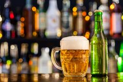 Jug of beer with bottle served on bar counter Royalty Free Stock Photos