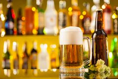 Jug of beer with bottle served on bar counter Royalty Free Stock Image