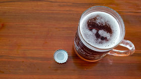 Jug with beer and openned bottle cap on wooden table Royalty Free Stock Image