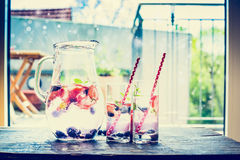 Jug with berries lemonade, ice cubes and glasses on table over terrace background. Royalty Free Stock Images