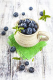 Jug of blueberries on white wooden table Royalty Free Stock Photo