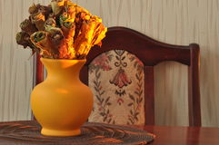 Jug with a bouquet of dried leaves resembling roses Stock Photos
