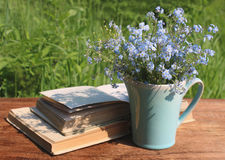 Jug with bouquet of forget-me-nots and books on wooden table Royalty Free Stock Photos