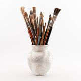 Jug with brushes. Jug with paint brushes on the wight background Royalty Free Stock Images