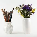 Jug with brushes and vase of wild flowers Royalty Free Stock Photos