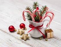 Jug with christmas candy canes on a wooden table Stock Photography