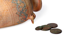 Jug And Coins. Ancient jug with a couple of coins over white background Stock Photography