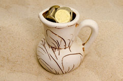Jug with coins in sand Stock Images