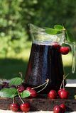 Jug with cold cherry juice, covered with droplets, next to a sweet cherry with leaves.  stock image