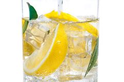In the jug is a drink of ice, the lobules of a fresh juicy yellow lemon and crystal clear water. In the jug is a drink of ice, the lobules of a fresh juicy stock image