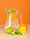 Jug with drink, orange and juicy lime Royalty Free Stock Photography