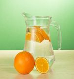 Jug with drink and oranges Royalty Free Stock Photo