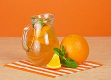 Jug with drink, ripe oranges, a striped napkin Stock Photo