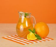 Jug with drink, ripe oranges and striped napkin Stock Photography