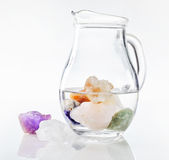 Jug of drinking water with healing stones. Transparent glass jug of drinking water with submerged healing stones and colorful minerals, isolated on white Stock Image