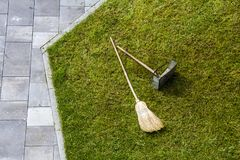 Jug dustpan and a broom on a green grass lawn. Gardening tools. Jug dustpan and a broom on a green grass lawn. Gardening tools Royalty Free Stock Photos
