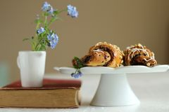 Jug with flowers forget-me-not on vintage book and croissants Royalty Free Stock Photo