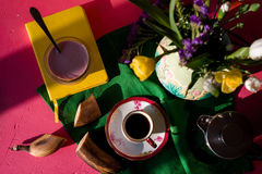 Jug with flowers, yogurt, cup of coffee on a napkin Stock Photos